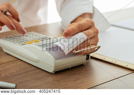 Closeup View Of Female Hands Using Adding Machine With Printout Receipt In A Tax And Accountancy Ima
