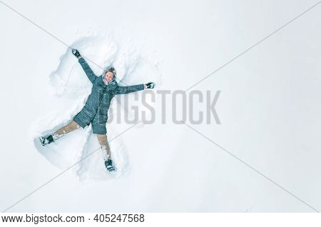 Young Beautiful Woman In A Gray Jacket, Light Pants, Boots Makes A Snow Angel In The Snow, A View Fr
