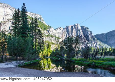 Charming little lake in the Yosemite Valley. The rock-monolith El Capitan is reflected in the smooth water. Yosemite Park is located on the slopes of the Sierra Nevada