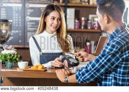 Asian Customer Man Paying With Credit Card Via Contactless Nfs Technology To Asian Barista Of Small