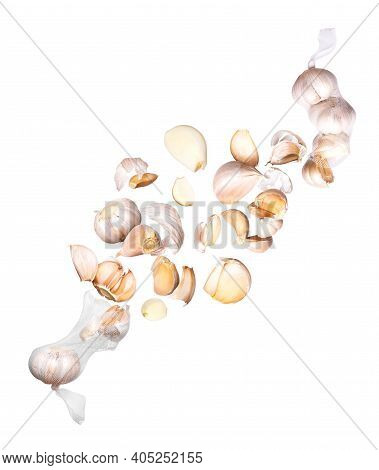 Garlic Cloves Fly Out Of Mesh Bags, Isolated On White Background