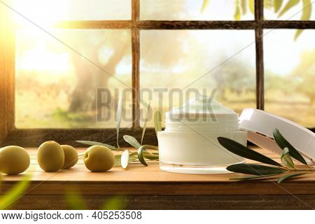 Natural Skin Cream With Olive Extract With Branch And Olives On Wood Table With Window Background An