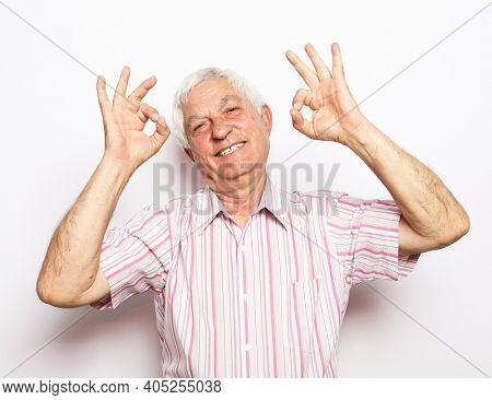 Emotion, lifestyle and old people concept: Portrait of energetic positive old man show okay sign over white background.