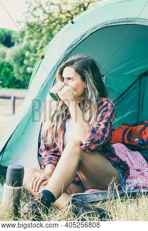 Caucasian Young Woman Drinking Tea, Sitting In Tent And Looking Away. Thoughtful Female Traveler Cam