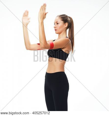 Fitness woman performs exercises for the muscles of the hands with resistance band. Photo of young female in fashionable sportswear on white background. Strength and motivation.