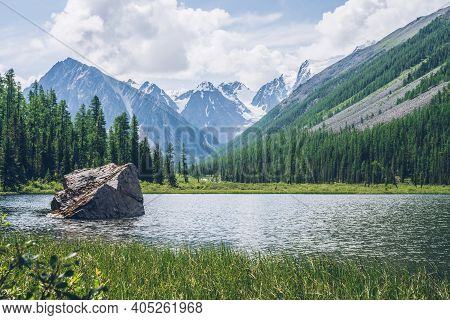 Meditative View To Beautiful Lake With Stone In Valley On Snowy Mountains Background. Scenic Relaxin