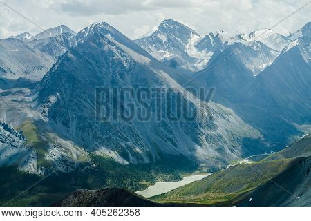 Awesome View To Mountain Valley With Lake And Huge Glacier Mountains Under Gray Cloudy Sky. Beautifu
