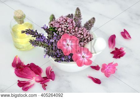 Natural herbal medicine with  flowers and herbs in a mortar and  pestle with oil bottle and rose petals on marble. Still life for naturopathic health care for aromatherapy essential oil preparation.