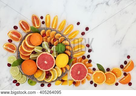 Healthy summer sunshine fruit with oranges, lemons, limes, grapefruit and cranberries high in antioxidants, anthocyanins, lycopene, fibre and vitamin c. Immune boosting health care concept. On marble.