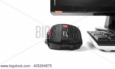 Computer Mouse On A White Table Near A Personal Computer.
