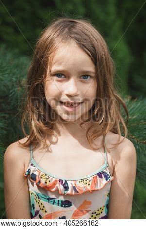 Outdoor portrait of elementary age girl smiling at camera showing missing baby teeth
