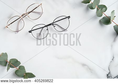 Woman's Eyeglasses And Eucalyptus Branches On Marble Background. Flat Lay, Top View.