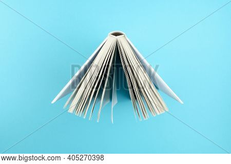 Directly Above View Of Top Of Open Hardcover Book On Blue Background