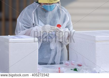Female Health Worker In Ppe Clothing Collects Sputum And Saliva Samples To Detect Covid-19 Infectiou