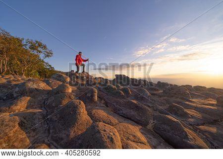 Tourist Asian Man Trekking, Traveling At Dry Rocks Stone In Lan Hin Pum, Phu Hin Rong Kla National P