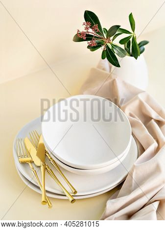 Minimalist Set Of Empty Crockery In Natural Day Light With Golden Cutlery. Beige And Earthy Colours.