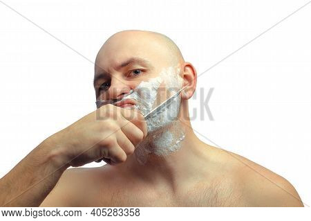 A Caucasian Man Tries To Shave With A Knife. A Brutal Bald Man Holds A Knife In His Hand And Shaves