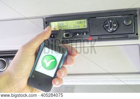Digital Tachograph And A Hand Holding A Download Key Device. Digital Tachograph Driver Card Ok Check