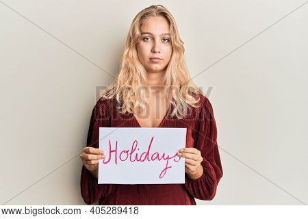 Young blonde girl holding holidays banner message relaxed with serious expression on face. simple and natural looking at the camera.