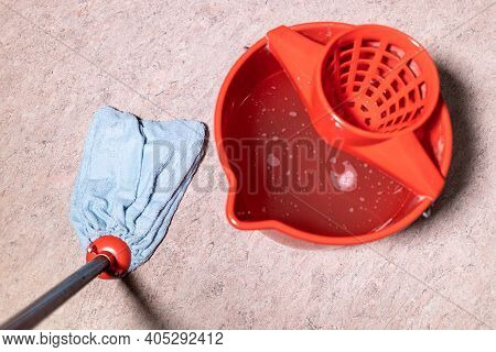 Point Of View Of Mop Cleaning Linoleum Flooring Near Red Bucket With Water At Home