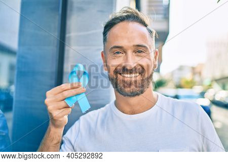 Middle age handsome man smiling happy holding blue prostate cancer ribbon at the city.