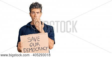 Young handsome man holding save our democracy protest banner covering mouth with hand, shocked and afraid for mistake. surprised expression