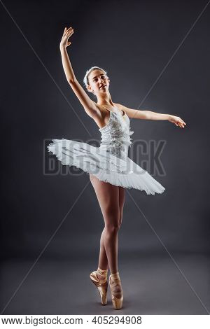 A Young Graceful Ballerina Dressed In Professional Attire, Pointe Shoes And A White Tutu, Demonstrat