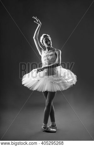 Portrait Of Ballerina In Tutu And Pointe Shoes Making A Beautiful Pose. Black And White Photography.