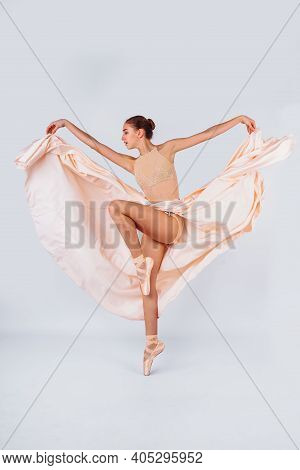 Free Flight. Graceful Classic Ballerina Dancing On White Studio Background. Pastel Beige Dress Cloth