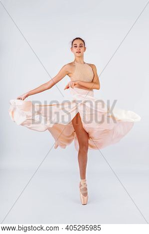 A Young And Incredibly Beautiful Ballerina Is Posing And Dancing In A White Studio Full Of Light. Th