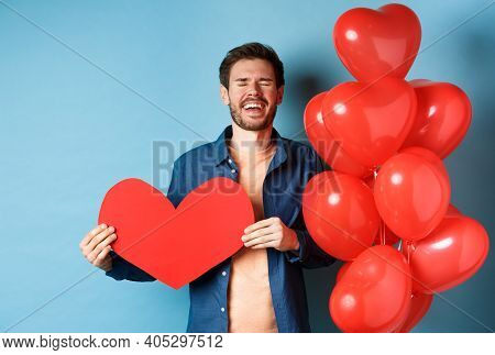 Heartbroken Man Crying Of Breakup Of Valentines Day, Holding Red Heart Cutout And Standing Near Roma