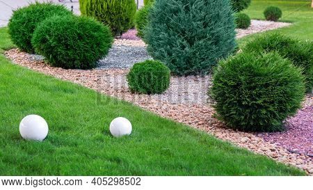 Landscape Bed Of Garden With Growth Arborvitae Bushes By Natural Rock Mulch Way On A Day Spring Yard
