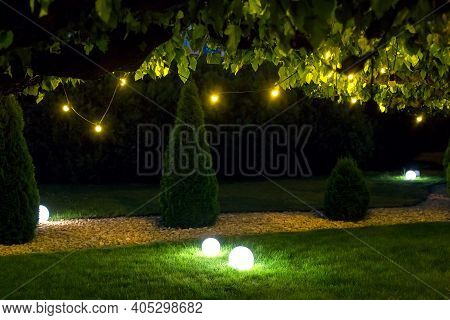Illumination Park Light Garden With Electric Ground Ball Lantern With Stone Mulch And Thuja Bushes I