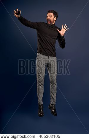 Mid-air Selfie. Full Length Of Handsome Young Man In Trendy Black Sweater Taking Selfie While Jumpin