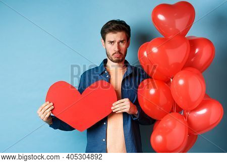 Sad Man Looking Heartbroken And Lonely, Holding Paper Red Heart And Standing Near Balloons Over Blue