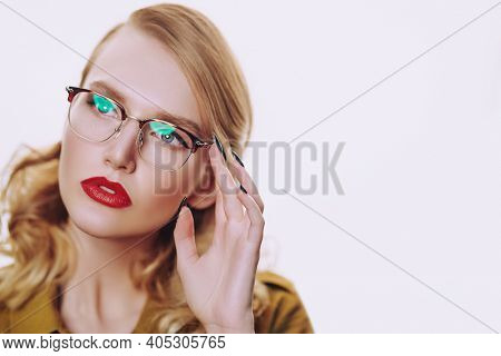 Optics, eyewear. Business style. Portrait of a fashionable blonde woman in elegant glasses. Copy space.