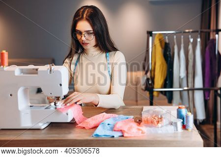 Pretty Dressmaker Woman Sews Clothes On Sewing Machine. In Process Seamstress In Workshop. Creating