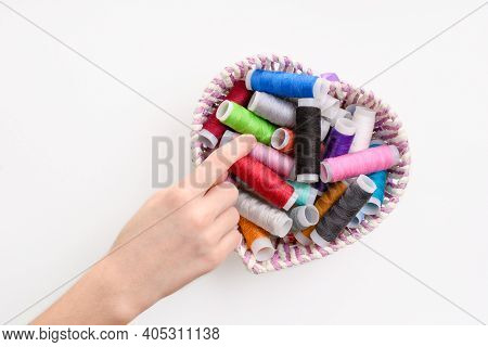 A Woman's Hand Takes A Red Spool Of Thread From A Basket Of Threads. The Process Of Selecting Thread