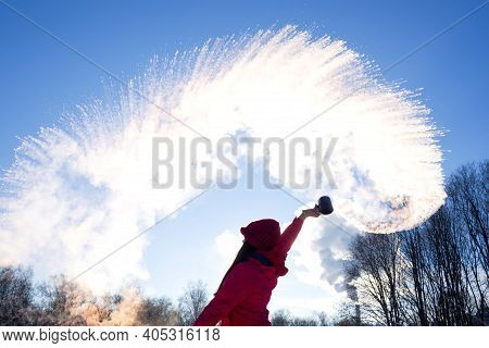 Person Pouring Hot Water Up In The Sky, Sunny Winter Day. Boiling Water Challenge, Which Instantly F