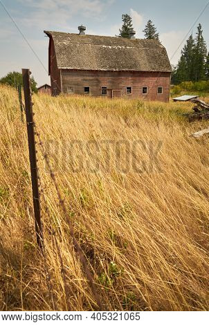 Rustic Barn And Dry Grass. A Faded, Red Barn In The Palouse. Washington State, Usa.