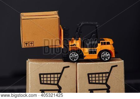 Toy Forklift With Carton Boxes On Keyboard Close-up. Logistics And Wholesale Concept