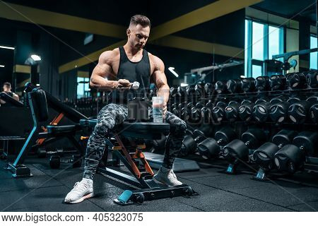 Athlete Man Preparing Protein Cocktail Or Use Sport Nutrition Supplement In Gym