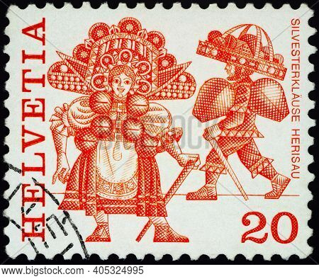 Moscow, Russia - January 20, 2021: Stamp Printed In Switzerland Shows New Year's Eve Costumes, Heris