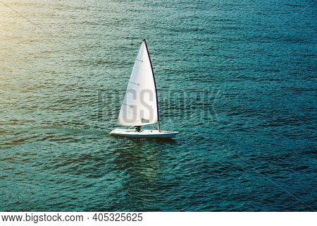 Sailing Boat In Open Sea At Sunlight. White Sail On Blue Water. Luxury Yacht In The Ocean. Aerial Vi