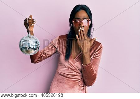 Young african american woman wearing sexy party dress holding disco ball covering mouth with hand, shocked and afraid for mistake. surprised expression
