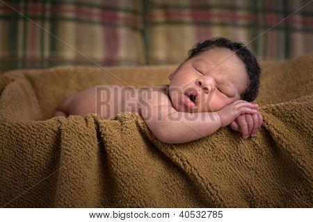Newborn African American Boy Closeup Sleeping in Basket with Brown Blanket, Shallow Depth of Field