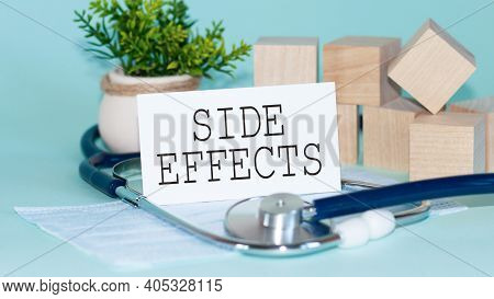Side Effects - Words Written On White Medical Card, With Medicine Mask, Stethoscope, Green Flower An