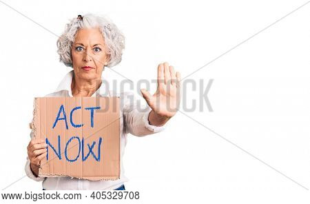 Senior grey-haired woman holding act now banner with open hand doing stop sign with serious and confident expression, defense gesture