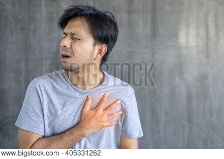Chest Pain, Young Asian Man Having Heart Attack, Man Suffering From Heartache Over Gray Background,