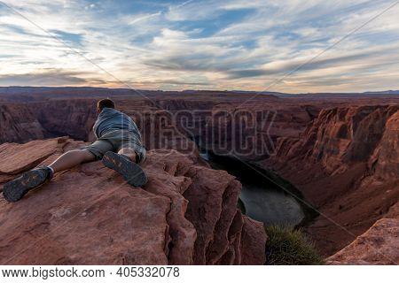 Horseshoe Bend, Arizona / Usa - October 30, 2014:  A Man Lays On The Edge Of Cracked Sandstone Cliff
